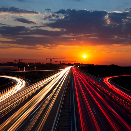 Speed Traffic at Sundown Time in the city - light trails on motorway highway at dusk,  long exposure, urban background