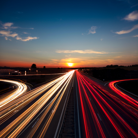 Speed Traffic  light trails on motorway highway at sundown,  long exposure, urban background with sun and dark sky