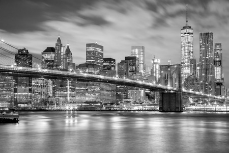 Manhattan skyscrapers and Brooklyn Bridge - city illuminations, black and white colors, New York, USA