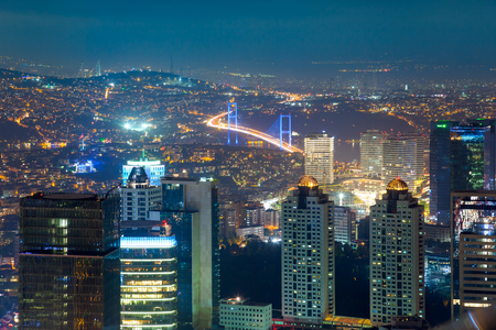 Night Aerial view of the illuminated city downtown, skyscrapers and bridge, Istanbul, Turkey, Europe - Asia