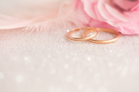 Gentle Wedding  Background with gold Rings, pink flower and light  feather on defocused sparkle Archivio Fotografico