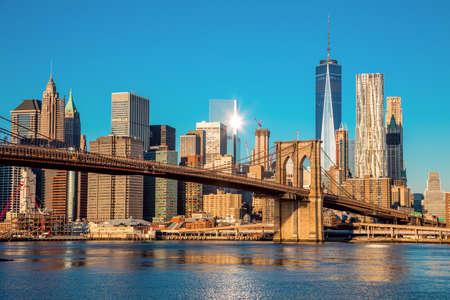 ダウンタウンのニューヨーク、ブルックリン橋、早朝の太陽の光、ニューヨーク市、米国のマンハッタンの有名なスカイライン