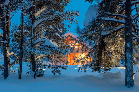 Wooden house with warm light in dark cold winter forest - Winter fairytale landscape 版權商用圖片 - 67935161