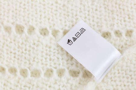 흰색 니트 양모 스웨터 배경에 세탁 태그, 큰 크기