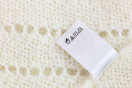 Laundry tag on white knitted wool sweater background, big size