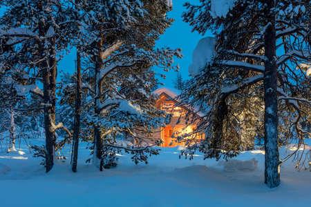 冬のおとぎ話の風景 - 夜の雪に覆われた冬の森、大きなサイズで暖かい光を用いた木造住宅