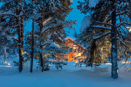 Winter fairytale landscape - Wooden house with warm light in night snowy winter forest, big size
