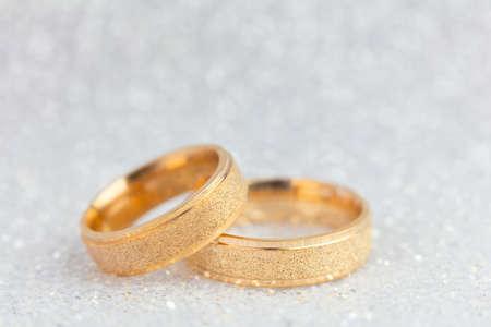 Sfondo di cerimonia nuziale frizzante - due anelli di nozze dorati su sfondo scuro brillante leggero