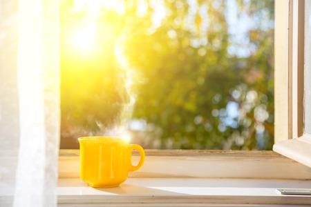 ¡Buenos dias! Taza en la ventana con sol y fondo de naturaleza desenfocada