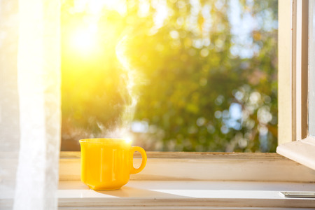 Goedemorgen! Beker op het raam met zon en intreepupil natuur achtergrond