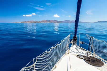 Sail boat, yacht - yachting in open blue sea near island, calm sunny weather, summer in Greece, Europe