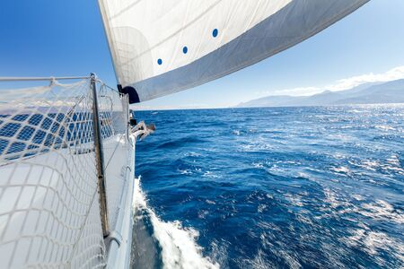 Sail boat, Sailing with fresh speed wind. A view from the yacht's deck to the bow and sails. Sail boat with set up sails gliding in open sea. Greece, Europe 写真素材