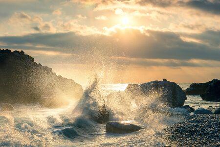Big Wave hit the rock at beach, sea water splash up to the sky with sun. Sunset Sundown at Sea. Storm. Seascape. 版權商用圖片