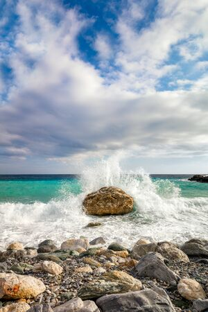 Big Wave hit the stone at beach, sea water splash up to the sky. Morning at Sea. Storm. Seascape.