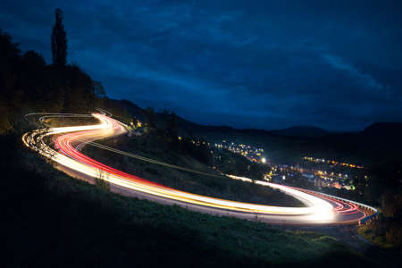 Long exposure - Car's Lights on the asphalt, at night on a mountain road, illuminated by the moon begins to rise over the horizon, a car making a turn, leaving behind a trail of light in the Mountains valley, night landscape