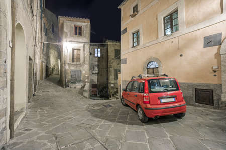 A typical Italian red car in a narrow street in an Italian old town at night. Sorano, Tuscany, Italy Reklamní fotografie