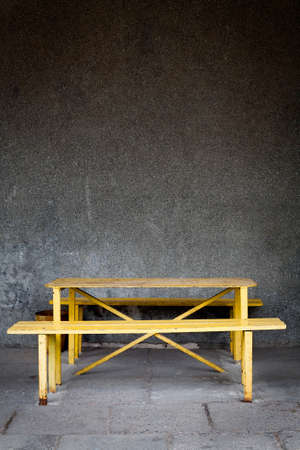 Old wall and yellow rusty table with a bench photo