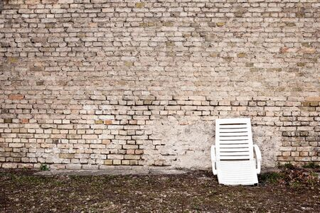 Aged wall and a broken plastic chair Stock Photo
