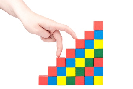 Female hand climbing upstairs which is made from wooden toy blocks  Imagens