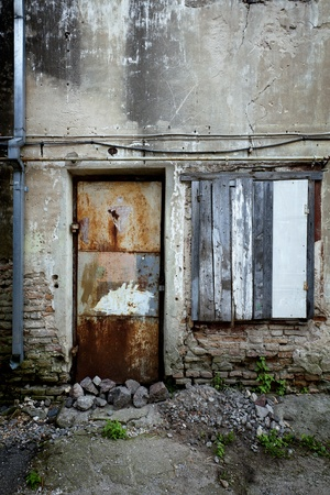 slum: Boarded up window and rusty door of a abandoned house Stock Photo