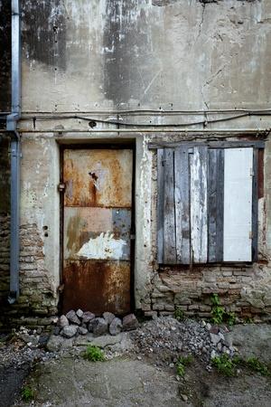 krottenwijk: Dichtgetimmerd raam en roestige deur van een verlaten huis Stockfoto