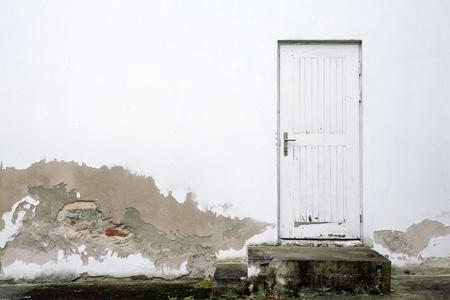 Antiguo muro de color blanco con puertas y los pasos