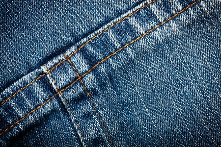 Worn blue denim jeans texture with stitch
