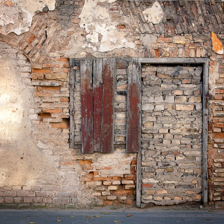 Old gungy wall with immured window and doors photo