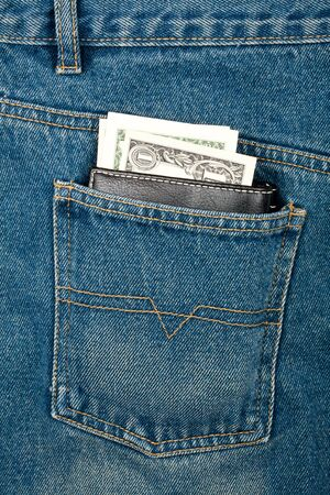 Black leather wallet with dollars in jeans pocket   photo