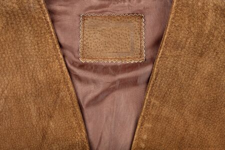 Fragment of brown suede vest with an empty label