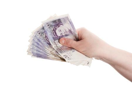 libra esterlina: Mano femenina sosteniendo veinte billetes de una libra aislados en blanco