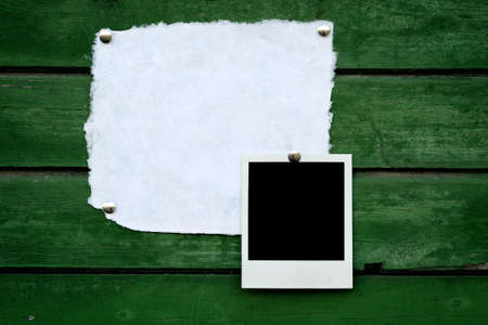 Handmade paper and instant photo on green wooden background  photo