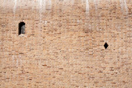 Brick wall with two small windows photo