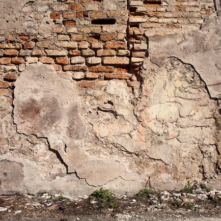 Old weathered wall of bricks and  ground  Foto de archivo