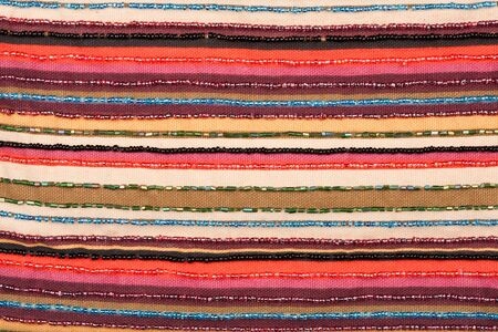 Colorful lined fabric texture with beads background  photo