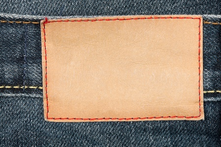 inner wear: Blank leather jeans label sewed on a blue jeans Stock Photo