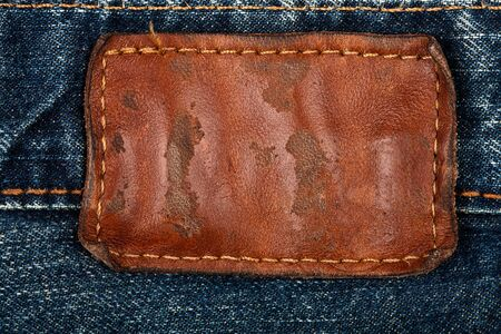 Blank grungy leather jeans label sewed on a blue jeans.  photo
