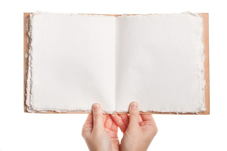 Opened book, made of handmade paper, in hands isolated on white background