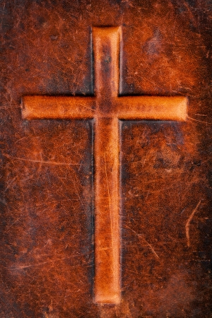 Cross symbol on a brown leather texture photo