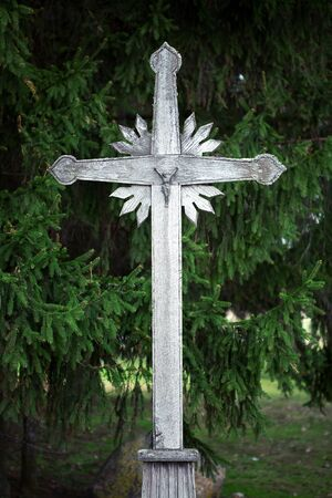 Old wooden cross with firs in background, Pasvalys Lithuania photo