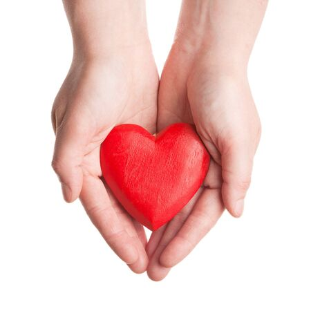 Red wooden heart in womans hands isolated on white  photo