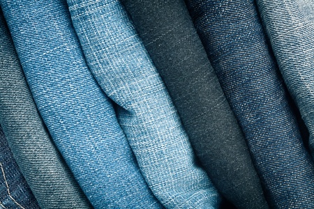 Stack of blue jeans as a background or texture   photo