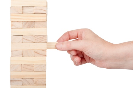 Wooden blocks tower and a hand isolated on white background