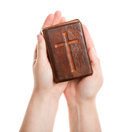 Hands holding the old bible isolated on white  photo