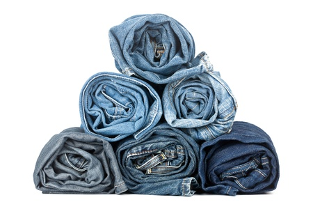 denim: Pila de pantalones enrollados sobre fondo blanco Foto de archivo