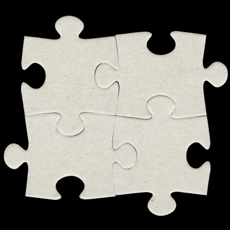 Four gray cardboard jigsaw puzzle piecies isolated on black photo