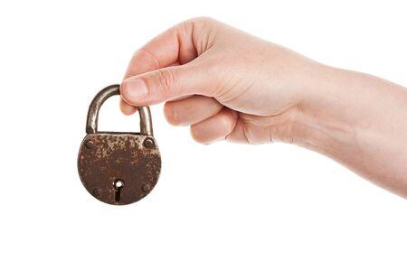 Hand holding rusty old padlock isolated on white  photo
