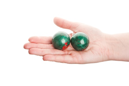 Green chinese balls in female hand isolated on white photo