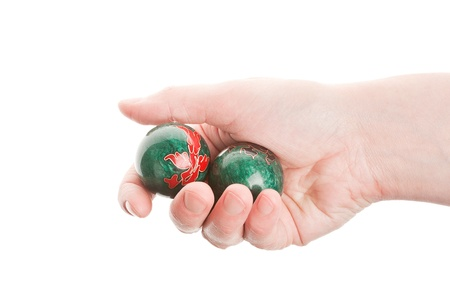 Green chinese balls in female hand isolated on white