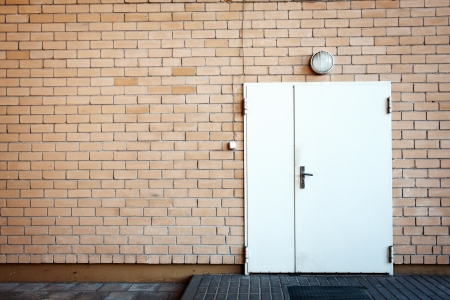 White painted metal door in a brick wall Stock Photo - 15277147